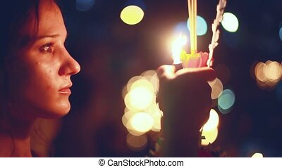 Young beautiful woman burns the candle in a carnival to...