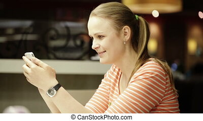 Young beautiful woman chatting on smartphone in cafe.