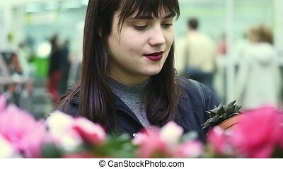 Young beautiful woman chooses flowers in a flower shop.