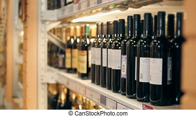 Young Beautiful Woman Chooses Wine In The Supermarket.