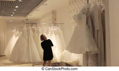 young beautiful woman choosing a white gown in a wedding shop. Wed concept