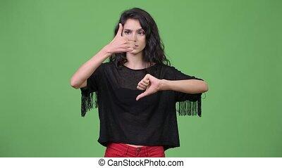 Young beautiful woman choosing between thumbs up and thumbs...