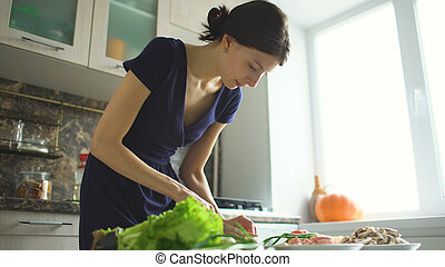 Young beautiful woman cook cutting the mushrooms on wooden board for pizza in the kitchen at home