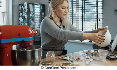 Young beautiful woman cooking at the kitchen, weigh the cocoa in kitchen scales and turning on the mixer.