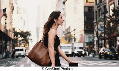 Young beautiful woman crossing the road in traffic downtown...