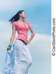 Young beautiful woman dancing against blue sky