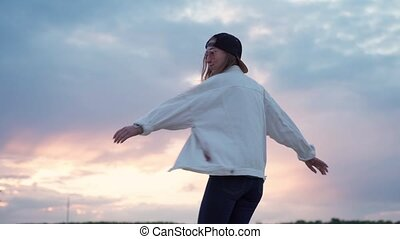Young beautiful woman dancing at sunset. Warm day and soft ...