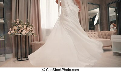 Young beautiful woman demonstrates white wedding dress during photo shoot in studio. Pretty female posing and moving her body in light room with sofa and flowers. Charming model dressed in stylish outfit poses and turns at modern interior. She has curly hair. Concept: bridal, elegant, style.