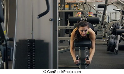 Young beautiful woman do exercise on Hamstrings in fitness club.