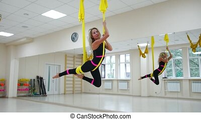 Young beautiful woman doing aerial yoga practice in purple...