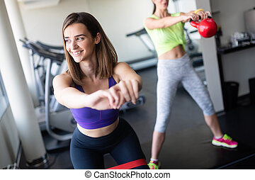 Young beautiful woman doing exercises in gym.
