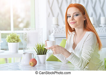 Young beautiful woman drinking coffee at home