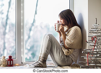 Young beautiful woman drinking hot coffee sitting on window sill in christmas decorated home