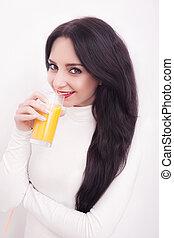 Young beautiful woman drinking orange juice on white background