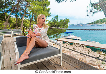 Young beautiful woman drinking white wine relaxing on open terrace enjoying view of the mediterranean sea in Croatia