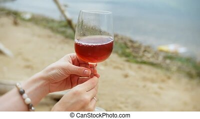 young beautiful woman drinking wine from a glass and walking along the sandy beach of the sea
