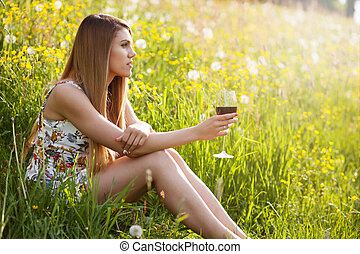 Young beautiful woman drinking wine outdoors
