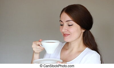Young beautiful woman drinks a hot drink from a white cup...