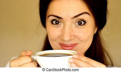 Young beautiful woman drinks a hot drink. The girl enjoys the aroma