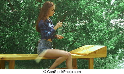 young beautiful woman drinks water on a bench in the park
