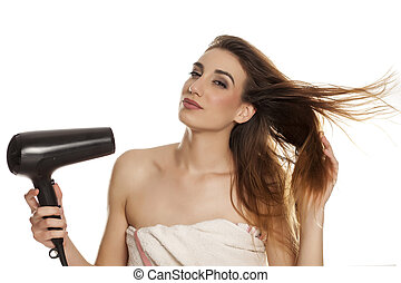 woman drying her hair with a blow dryer