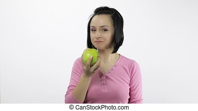 Young beautiful woman eating big, and juicy green apple on white background