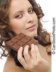 Young beautiful woman eating chocolate