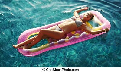 Young beautiful woman enjoying summer on inflatable mattress...