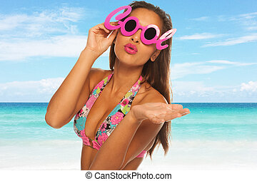 Young beautiful woman enjoying the sun on the beach wearing cool glasses