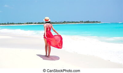 Young beautiful woman enjoying vacation on white tropical beach. Girl walking by the sea. SLOW MOTION