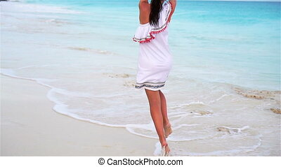 Young beautiful woman enjoying vacation on white tropical beach