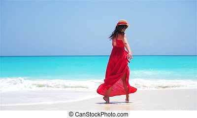 Young beautiful woman enjoying vacation on white tropical beach