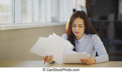 Young beautiful woman examines different documents in office.