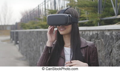 young beautiful woman getting experience in using VR-headset or virtual reality headset outdoor