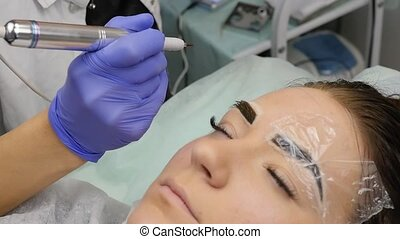 Young beautiful woman getting eyebrows tattoo. permanent...