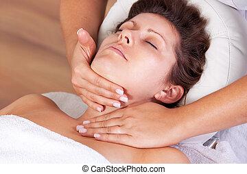 Young beautiful woman getting facial massage