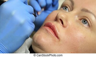 Young beautiful woman getting lips tattoo. permanent makeup...
