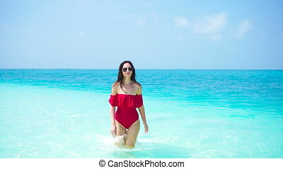 Young beautiful woman have fun on tropical seashore. Happy girl enjoy her tropical vacation exotic island
