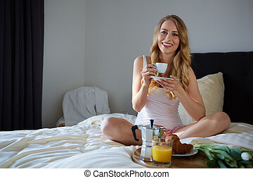 Young beautiful woman having breakfast
