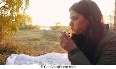 Young beautiful woman having hot tea at sunset relaxing and enjoying nature scene in slowmotion. 1920x1080