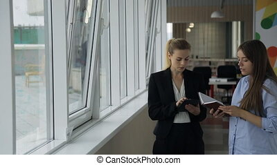 Young beautiful woman head of office listens to employee on work carried out near a window.