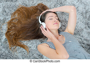young beautiful woman headphones listening music on the floor