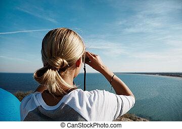 young beautiful woman hiker looking through binocular on mountain in summer