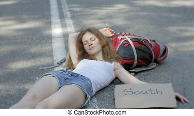 Young beautiful woman hitchhiking standing on the road with...