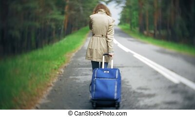 Young beautiful woman hitchhiking standing on the road with a suitcase on a table with an inscription SEA