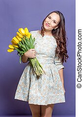 Young beautiful woman holding a bouquet of yellow tulips. Spring.