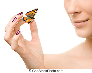 Young beautiful woman holding a butterfly
