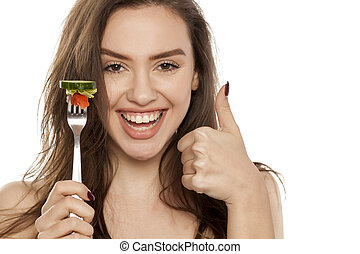 Young beautiful woman holding a fork with salad