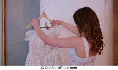 Young beautiful woman holding a hanger with cloth. Beautiful bride preparing wedding dress for ceremony.