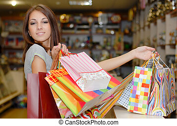Young beautiful woman holding bags
